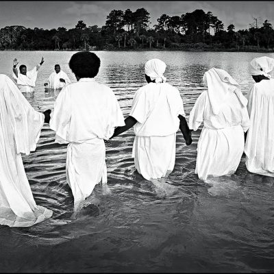 The faithful wade into Clear Lake for a total submersion baptism ceremony in Cocoa, Florida.