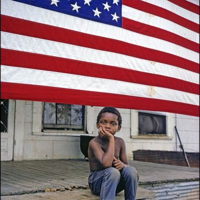 Young boy sits on his front porch in Mound Bayou, Mississippi.  The flag covered his oldest brother's military coffin when his body came home from North Viet Nam.  The boy's mother kept the flag on the front porch to keep her eldest son's memory close to the family.