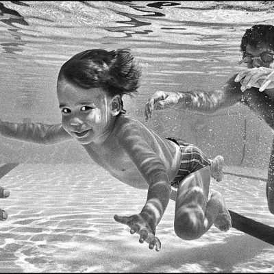 A young boy learns to swim underwater with his eyes open.